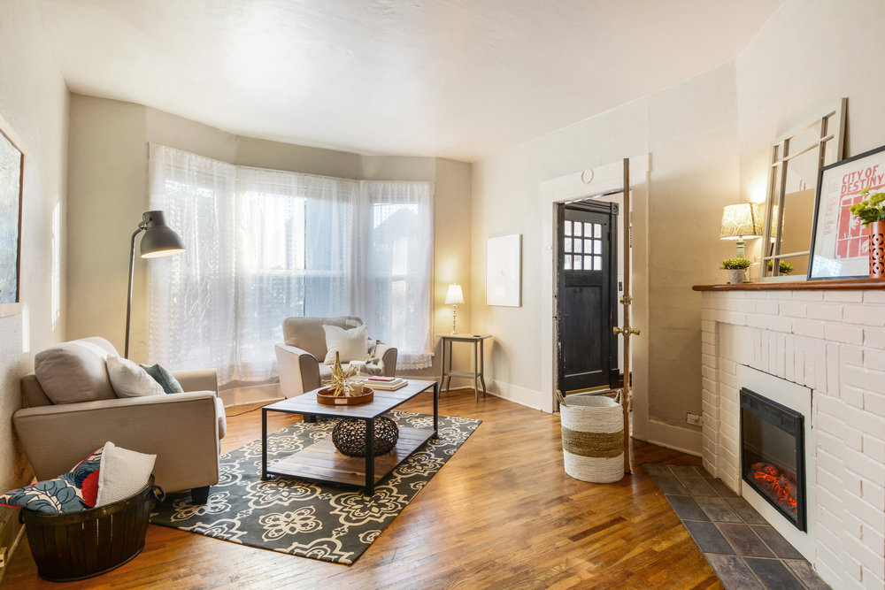 Main floor apartment with bay window, hardwood floor, fireplace, and its own interior front door from the shared entry area.