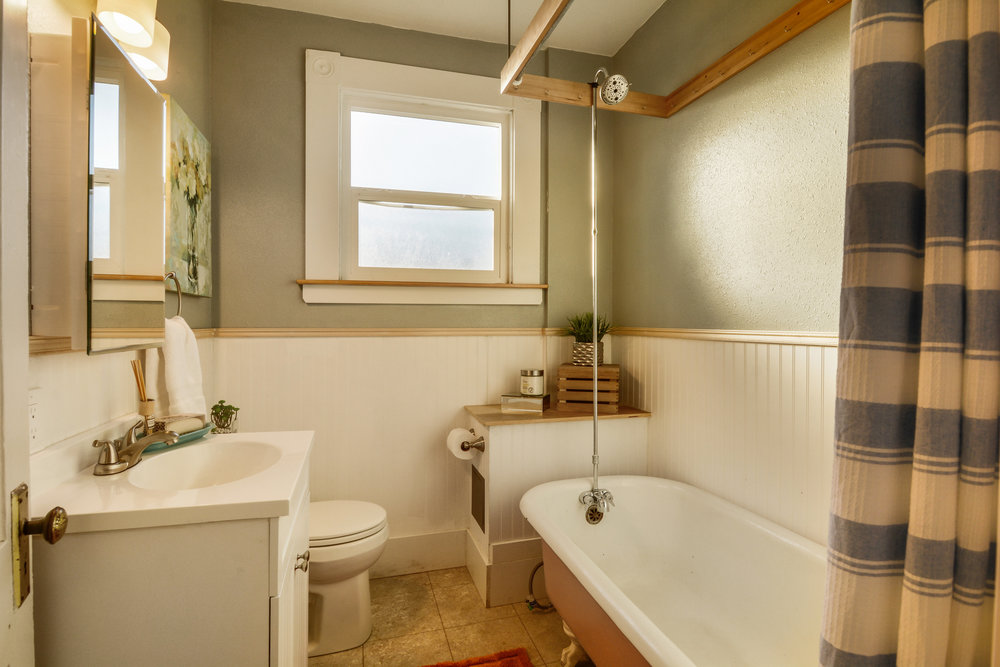 The upstairs apartment has a full bath with a clawfoot tub, wainscot, a window that easily slides open, and storage within the vanity and mirror cabinet.