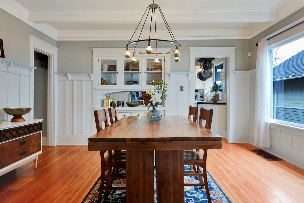The dining room is bright and full of Craftsman details like the boxed beam ceiling, wainscot, plate rail, and built-in buffet.