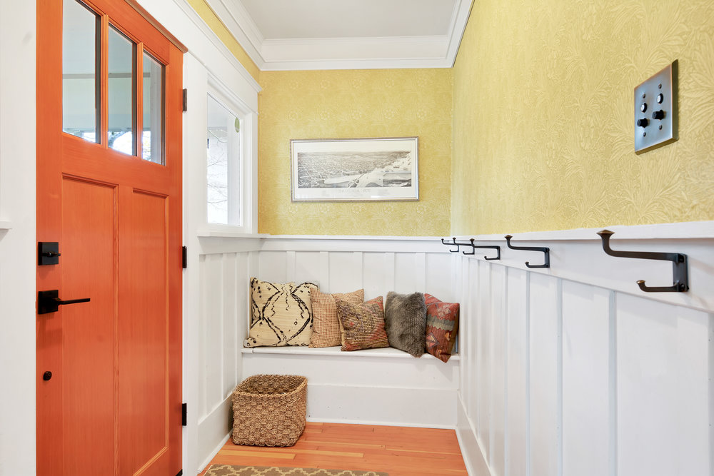 Wainscoted entry offers hooks for coats and bags, and a bench for removing shoes.