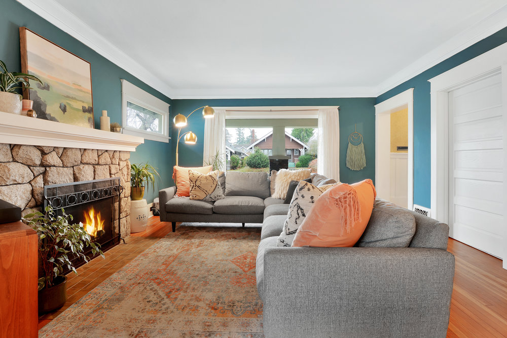 Spacious living room with granite fireplace, fir floors, pocket door, and picture window.