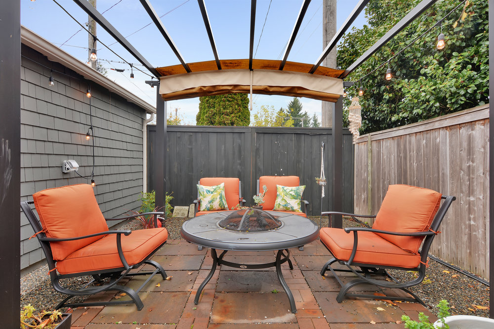 The fully fenced back yard includes this patio area with a pergola. The pergola cover may be drawn over on sunny days when shade is needed.