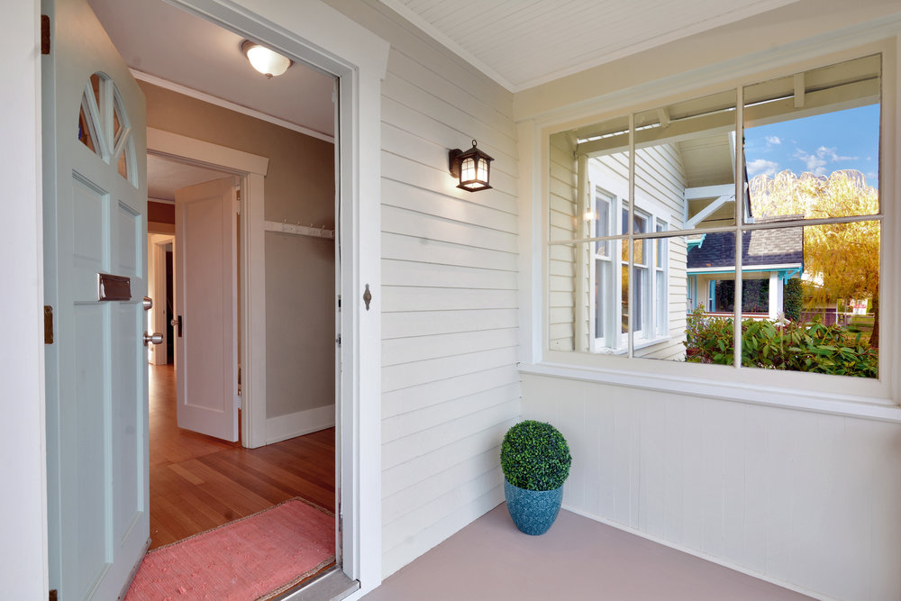 The covered porch is well-lit and is protected from weather by windows on two sides and opens into the front entry hall.