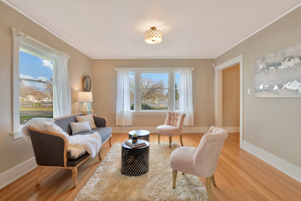 The living room features large windows facing north and east that easily open for fresh air.