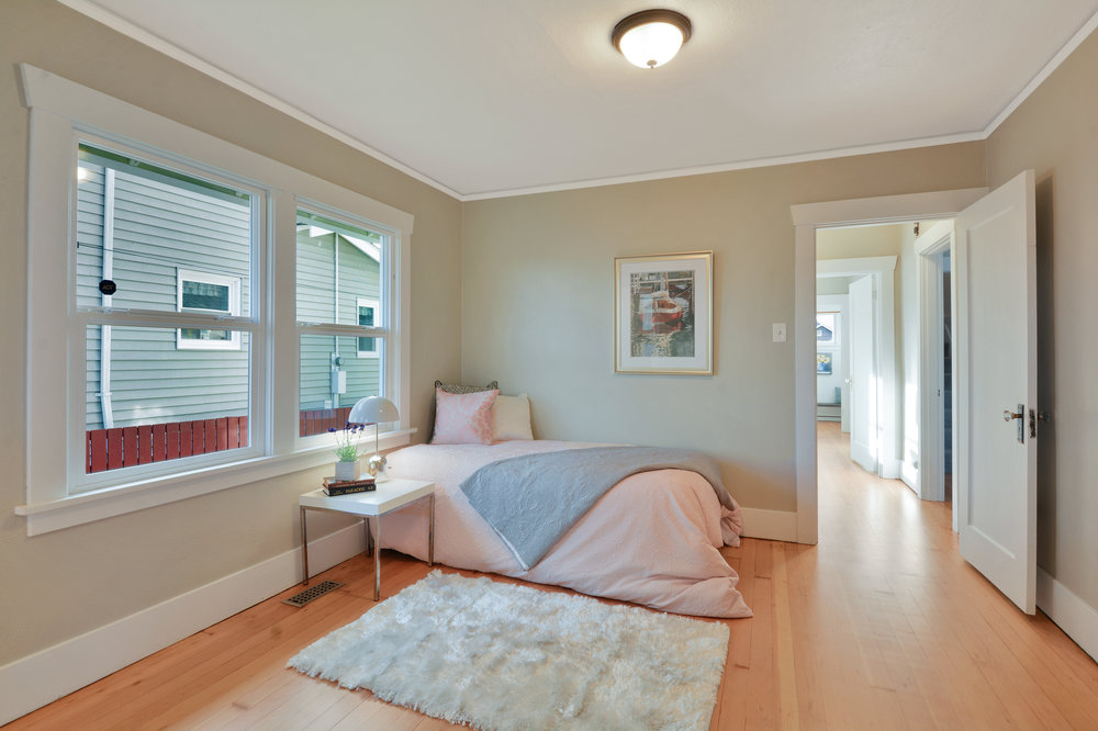 This second main floor bedroom with refinished fir floors, crown molding, and south facing windows is located near the front of the house.