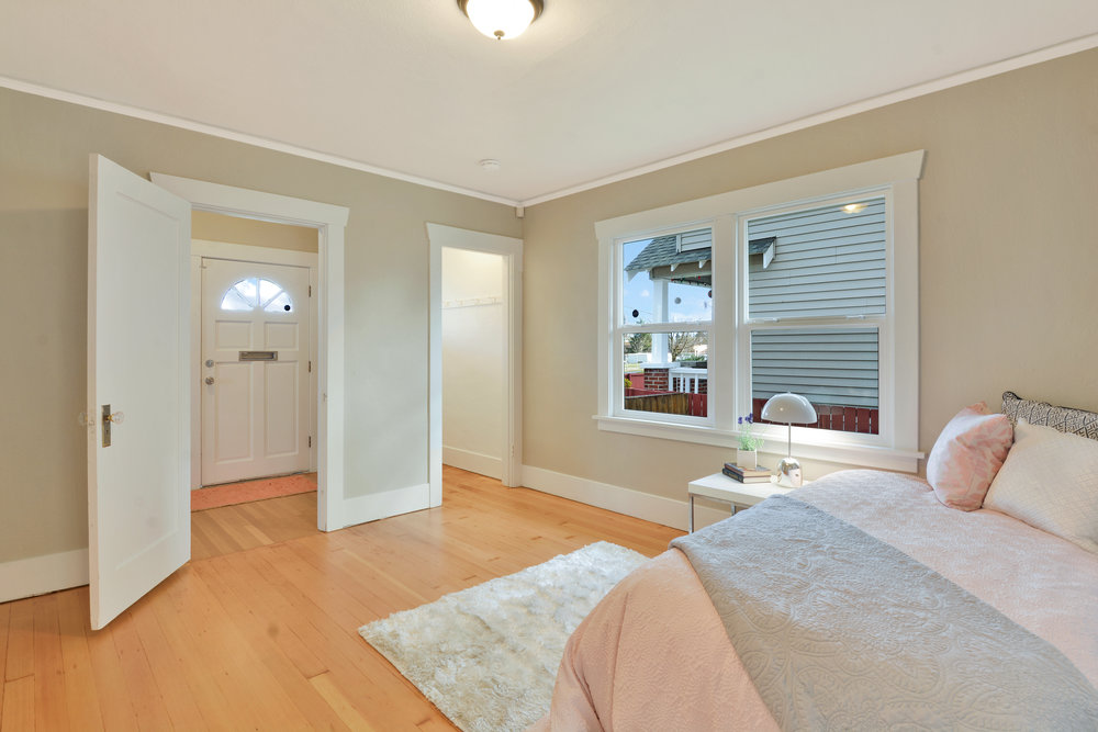 The second main floor bedroom with a door opening into the front hall and the closet shown on the right.