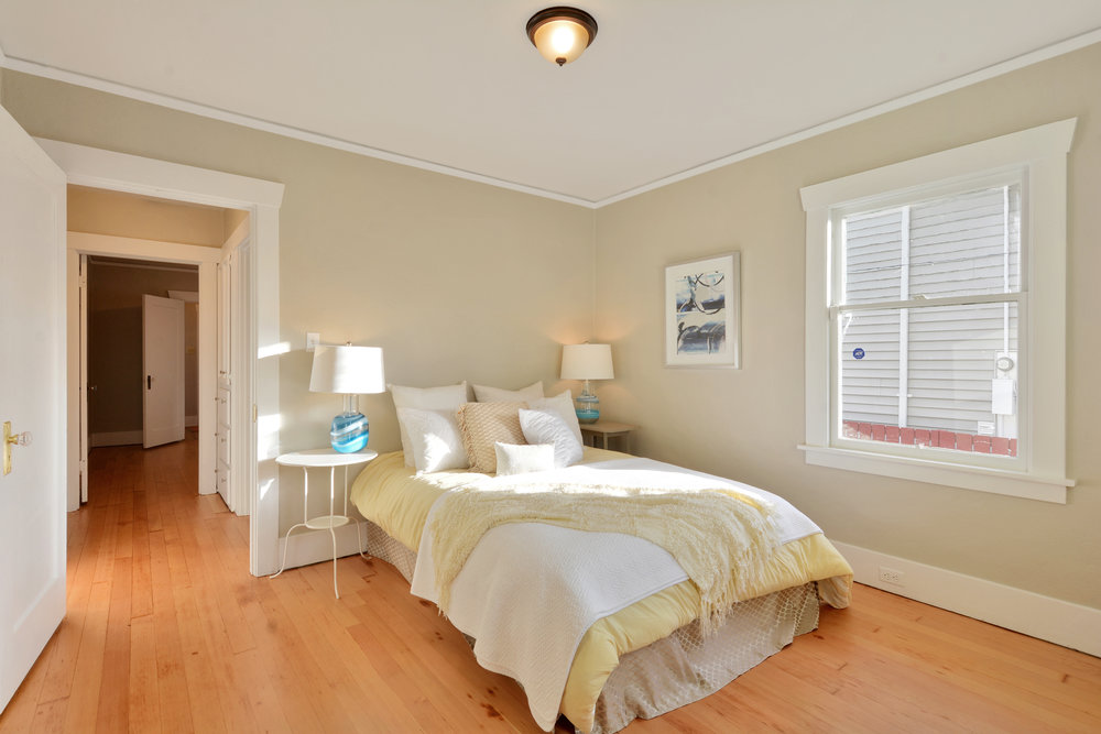 Another view of this bright main floor bedroom at the back of house with a view down the hall into the second main floor bedroom.