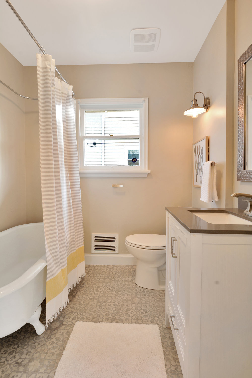 The full bath, located between the two main floor bedrooms, features a claw foot tub, brand new vinyl floor, and a vanity with undermount sink and cupboard below. A linen closet just outside the door offers additional storage.