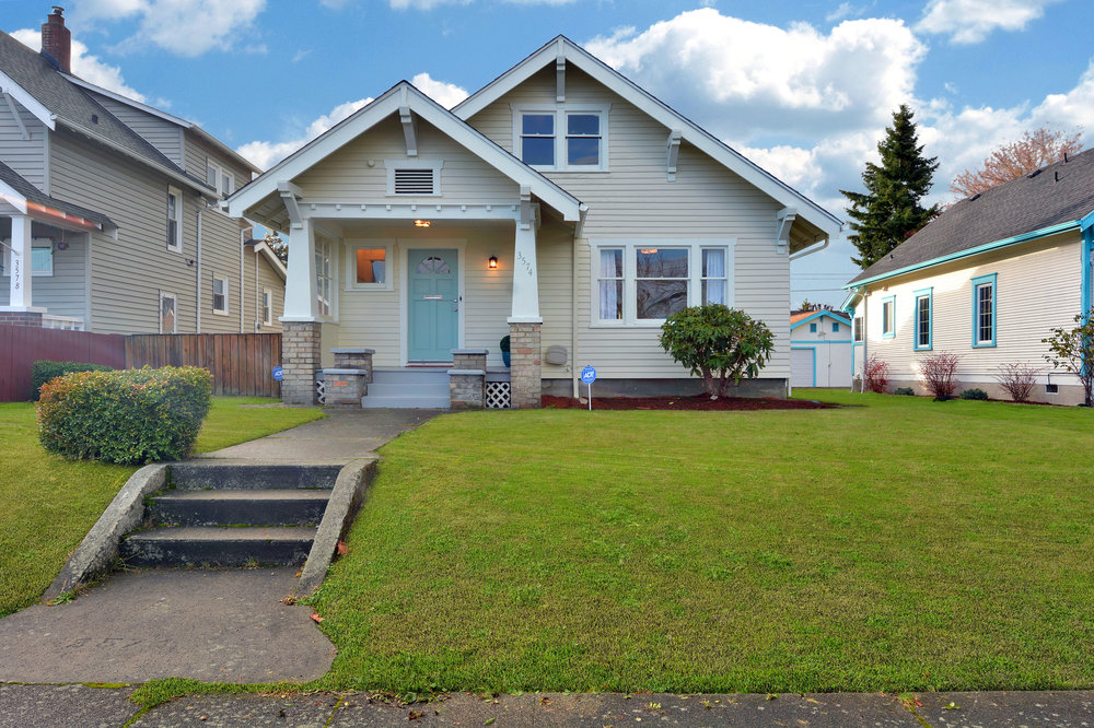 This freshly painted Craftsman home faces east onto South D street with a front lawn gently sloping up toward the covered front porch.