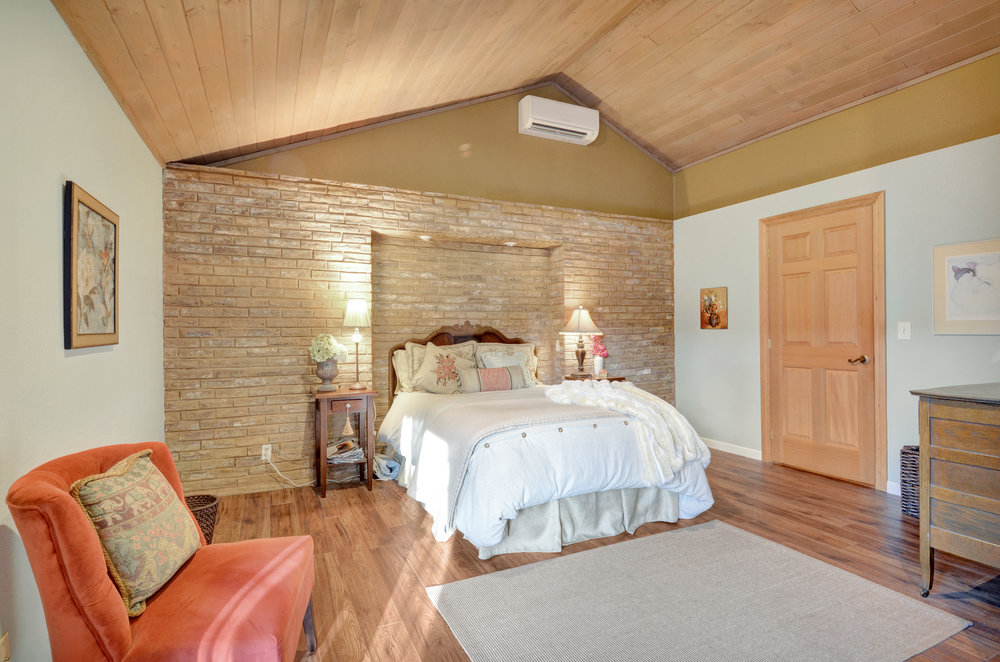 Spacious bedroom with wooden vaulted ceilings, brick accent wall, beautiful new engineered hickory wood floors, walk-in closet and French doors that open onto the back patio.