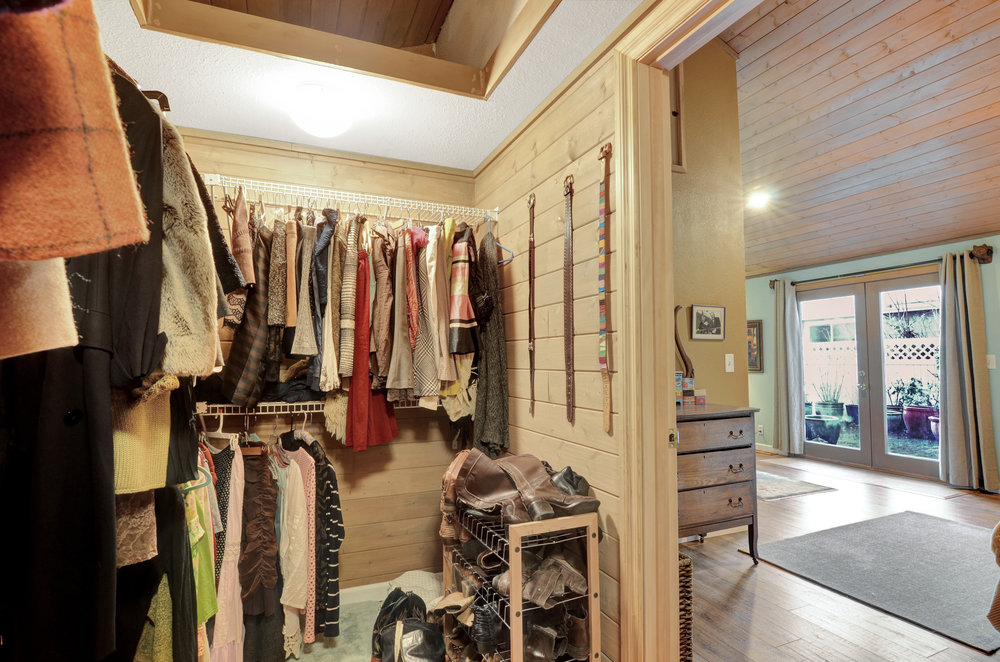 Walk-in closet with pretty wooden walls and plenty of space!