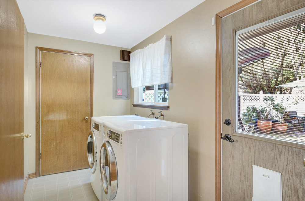 The laundry room is adjacent to the kitchen and family room with a door to the back patio. Newer high-efficiency washer and dryer stay with the home.