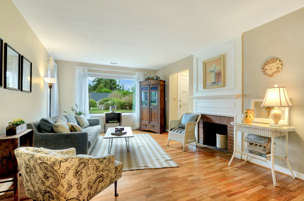 Smooth ceilings, refinished oak floors, new custom window blinds, and a cozy hearth create a beautiful living room.