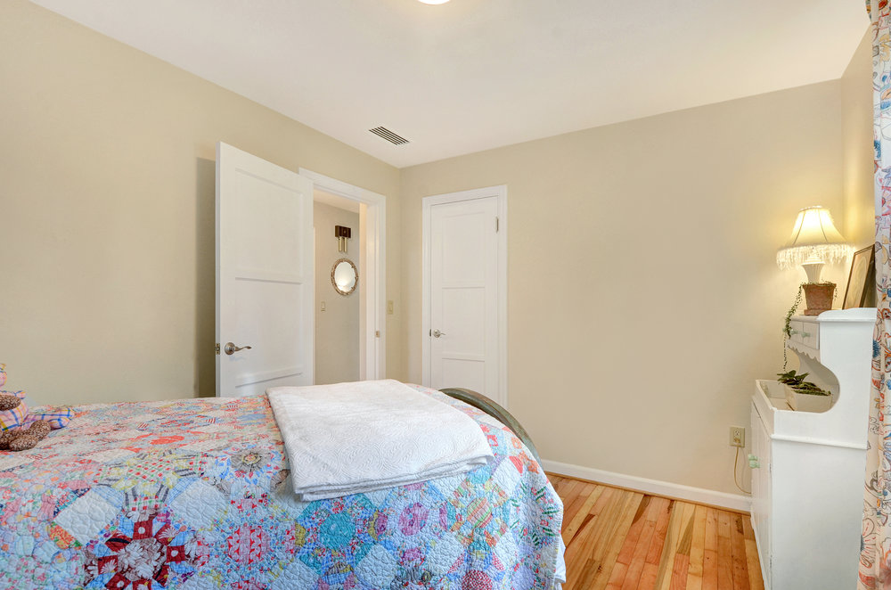 The warm coloring of the refinished fir floors contrasts nicely with the bright trim paint. One door opens into a closet, the other out into the hall where the bathroom is located.