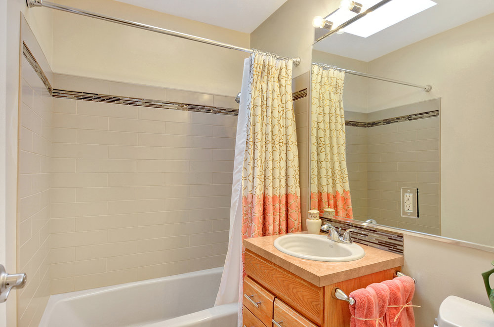 The full bathroom is updated with new floors, new Wilsonart counter, new tile in the tub and vanity backsplash, new tub, sink and faucet.