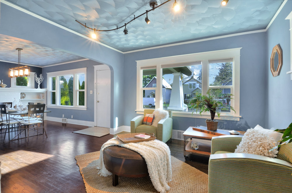 Ornamental comb textured ceilings, fresh paint, custom stained hardwood floors, and big front windows create beautiful living and dining rooms.