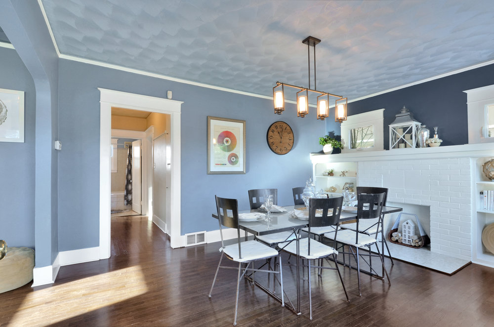 Open and bright with a white brick hearth, this dining room features an artistically textured ceiling, built-ins and those sweet windows that can open above the mantle.