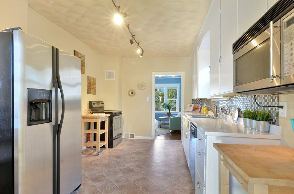 A spacious kitchen with stainless appliances, fresh paint, bright light, and new quartz countertops.