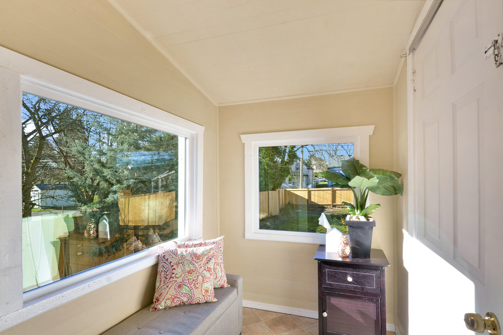 A sunny little enclosed porch with a door into the kitchen and a door to the short flight of stairs leading to the back yard. Use it as mud room for boots and brooms, or keep it sweet as shown here.