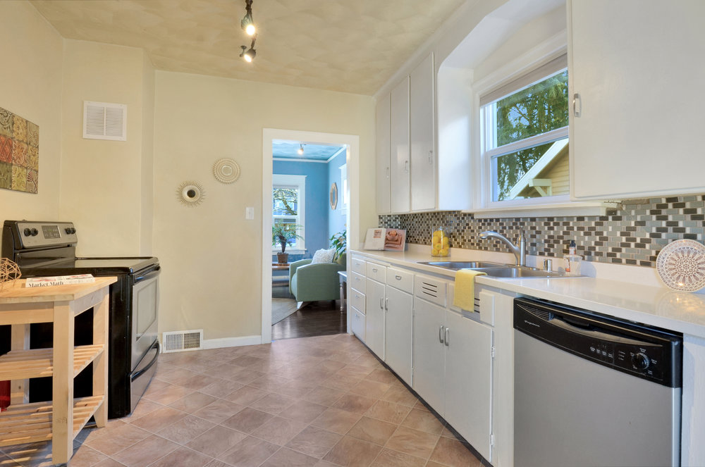 Details like the decorative tile backsplash, quartz countertop, and ornamental comb textured ceiling, dress up this practical, well-appointed kitchen.