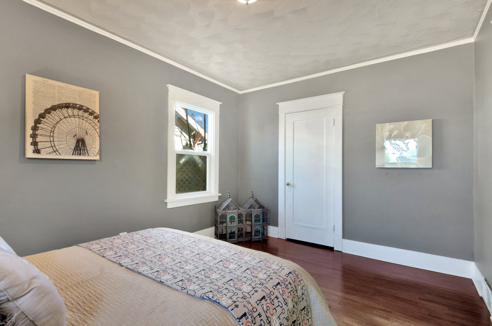 Calm colors, fresh paint, and classic details in the trim, floor, and ceiling create a very pretty bedroom.