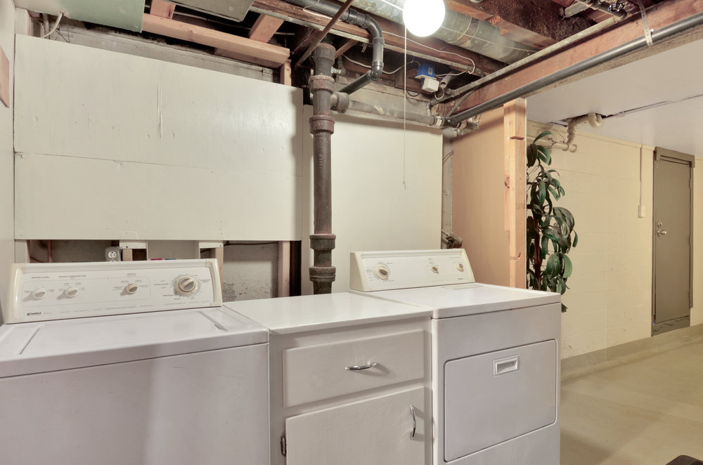 The laundry area near the full bath, featured washer, dryer, and convenient cupboard. A utility sink is just around the corner.