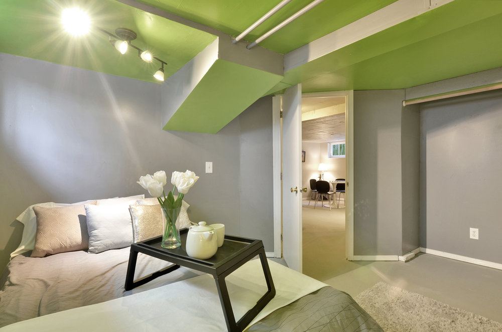 This basement bedroom is warmed up with cozy rugs, and bright lights. The stairs up to the main level are just outside the bedroom door, and the 2nd full bathroom is close by!