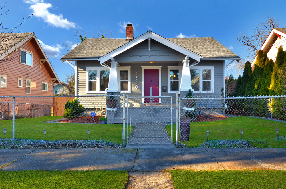 A nice feature of this neighborhood is the paved sidewalks with the planting strip giving even more space between the front of the homes and the curb. Here you can see the front fence, as well as the side hedge, and get another look at the classic curb appeal of this Craftsman home.