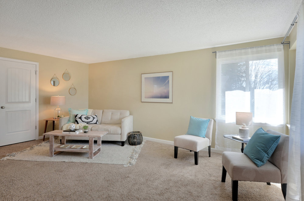 The living space is open to the kitchen so guests and family can socialize easily, or parents can keep an eye on kids while working on dinner. The door to the left opens into a coat/storage closet.