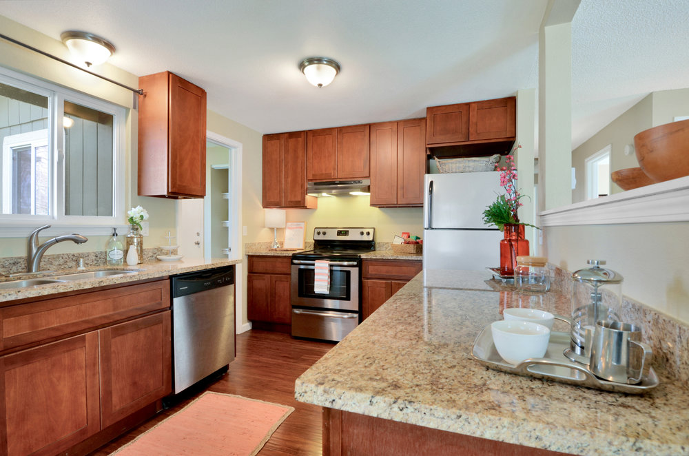 Open kitchen with granite counters, engineered hardwood floor, undermount sink, and a full set of silver finish appliances (refrigerator, stove, vent, and dishwasher). Great amount of counter space!