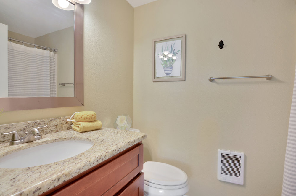 A full bath is accessible just down the hall from the living room and near the bedrooms. A shower/bath combo is lined with a tub surround and the undermount sink on the vanity makes for easy cleaning.