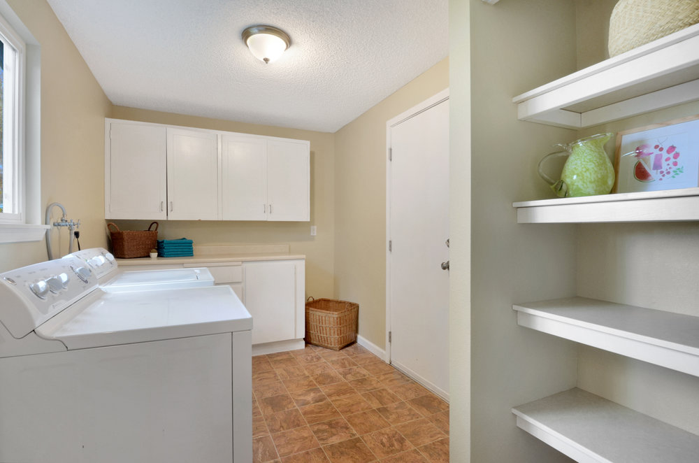 Brightened by a window to the back yard, and with a back door that leads into the attached garage, this laundry room is all set with washer, dryer, folding counter, storage cupboards, and pantry shelves.
