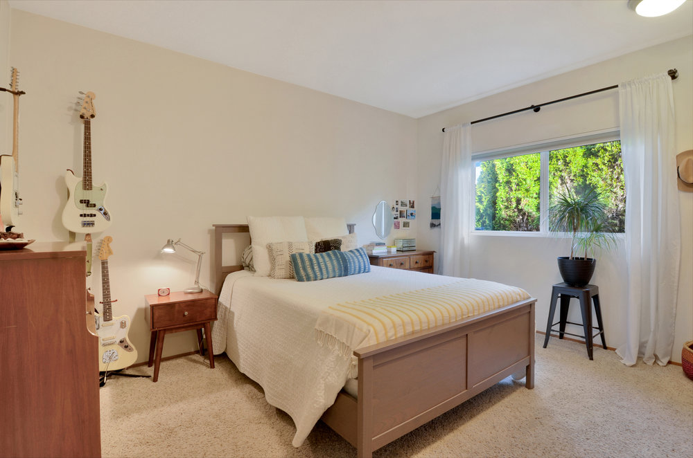 Along with a large clothes closet, this en suite bedroom features the high ceilings and bright neutral color palette found throughout the home.