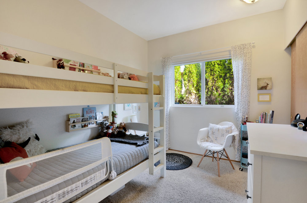 Just down the hall find this 2nd of 3 bedrooms perfect for kids, teens, or guests. Window faces north toward the side yard and hedge.