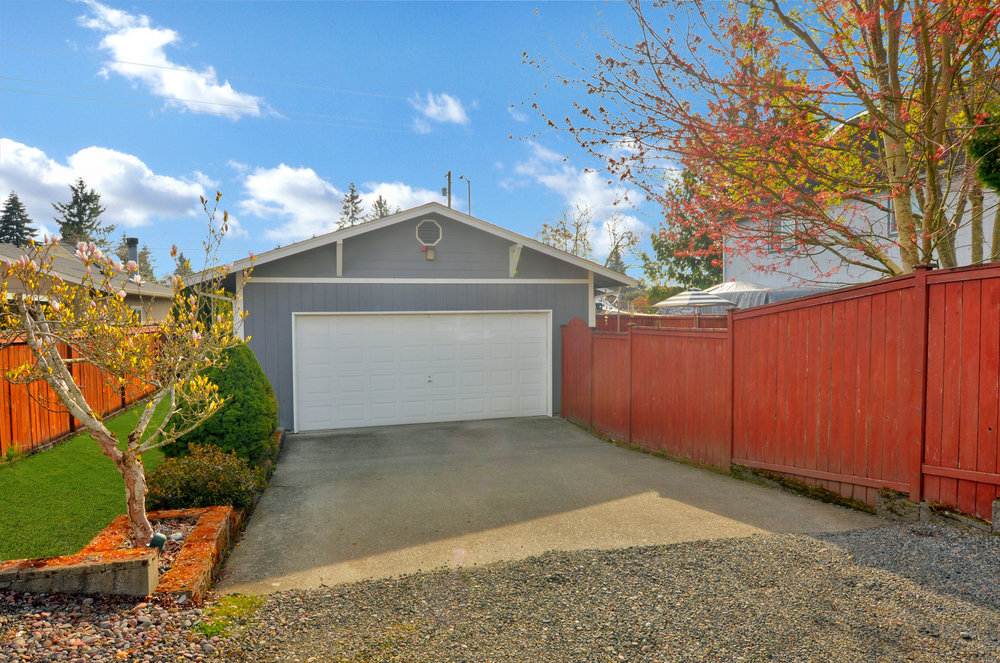 A paved driveway leads from the alley on the west side of the lot into the 2 car garage. A magnolia is just starting to bloom in the side yard on the left, and a wooden gate leads into the back yard on the right beside the garage door.