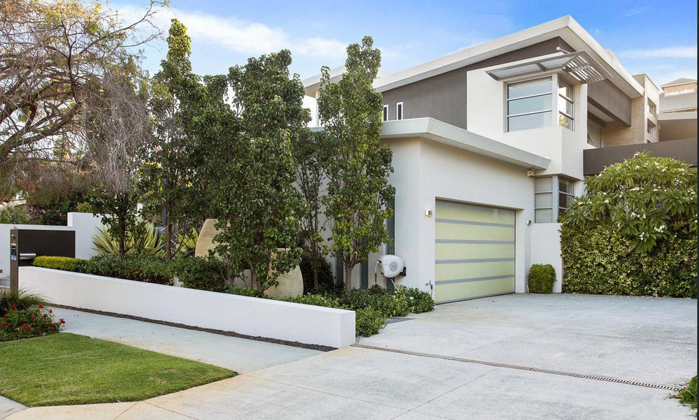 Action Cottesloe image of the home as it is today. The front entry is a perfect example of a home softening into its surrounds. The growth of the garden balance out the retaining walls required on the sloped block and creating a natural privacy screen.