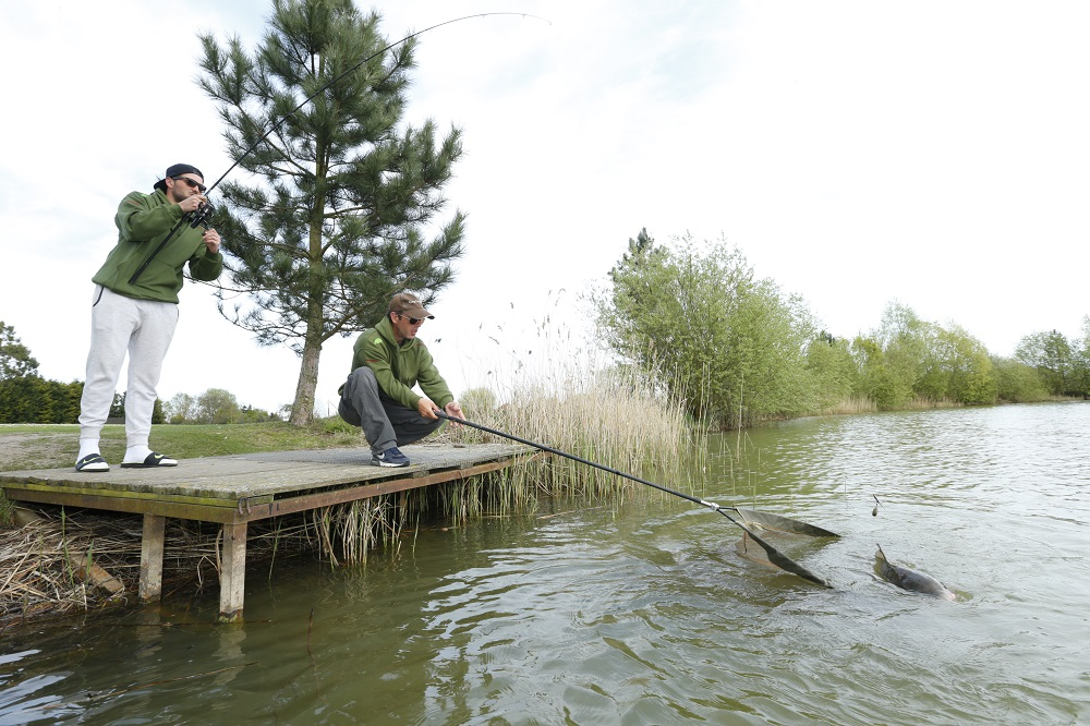 Ricky brings a fish to the bank in front of the Carpfeed cameras