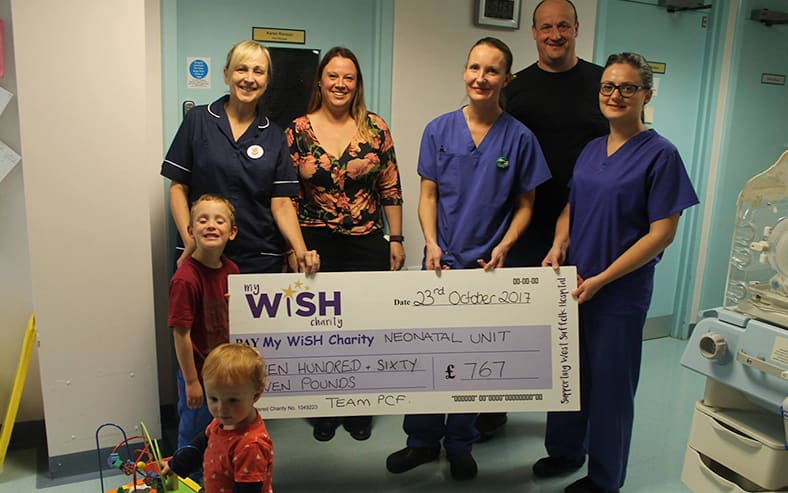 Matchwinner Phil Bowers (back right) and wife Heather present cheque to SCBU nurses