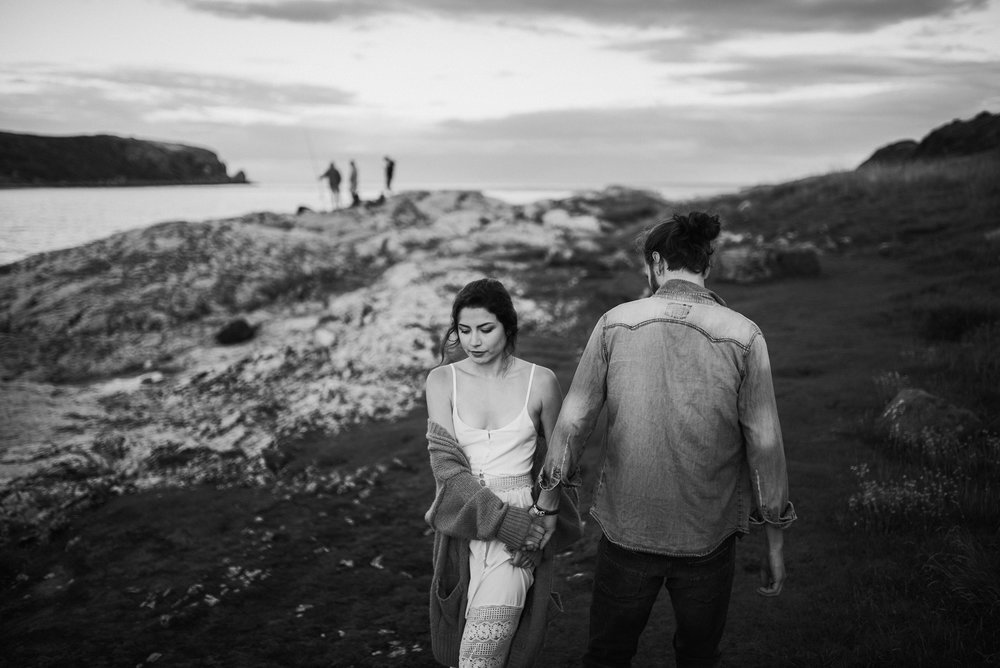 black and white photo of the couple walking on the northern Irish coast.jpg