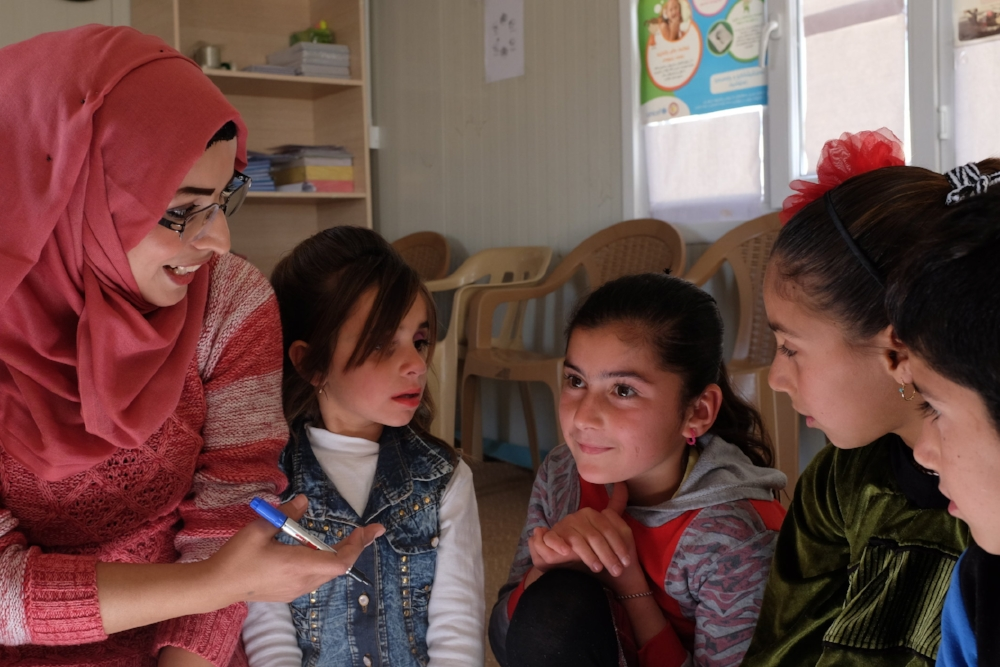 Yazidi children discussing pain points and coming up with design ideas during a co-creation session.