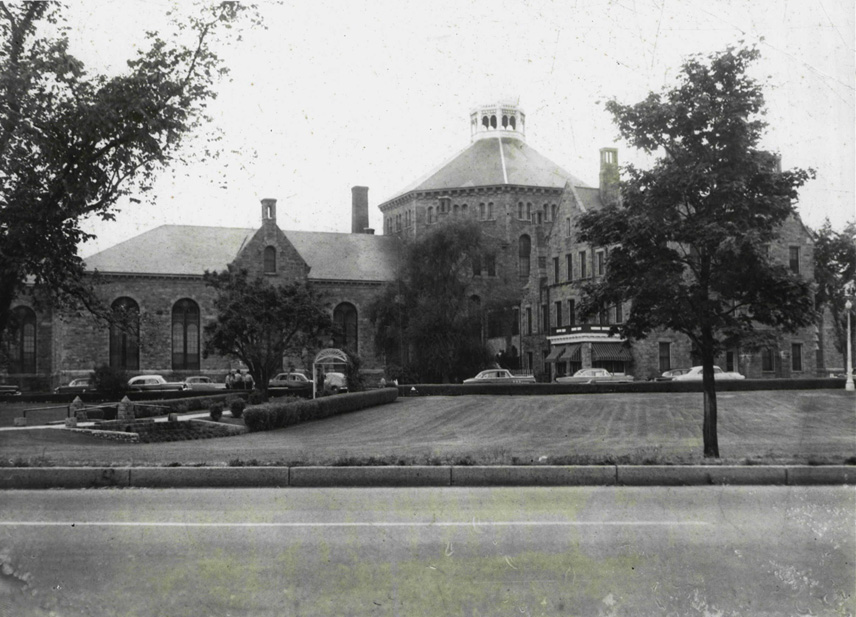 The Rhode Island Adult Correctional Institutions' maximum-security building in 1955. The warden's quarters are to the right, covered by the tree. The inmates are housed in the building to the left. Courtesy of J.R. Ventura and the Rhode Island Department of Corrections. Photo provided by Captain Walter Duffy.