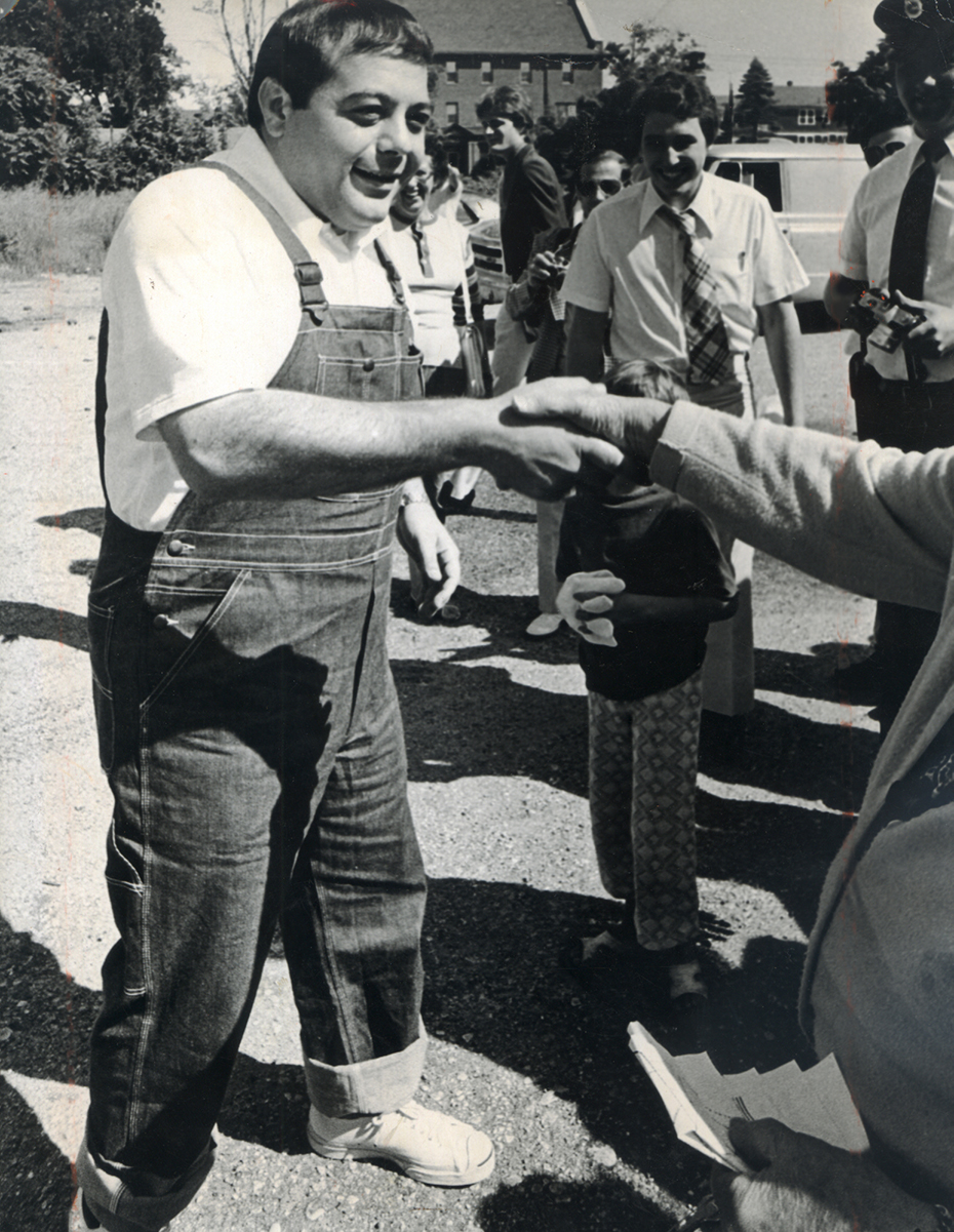 Wearing a new pair of overalls, Buddy shakes hands as he arrives for a neighborhood cleanup in August 1975.  Providence Journal file photo .