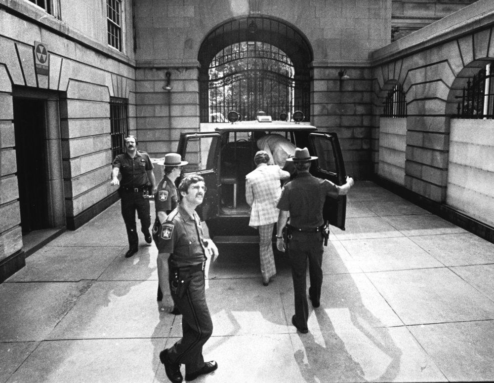 In August 1979, Jerry Tillinghast climbs into a van at Superior Court on his way to prison for the murder of George Basmajian. Courtesy of the Providence Journal/Michael Delaney.