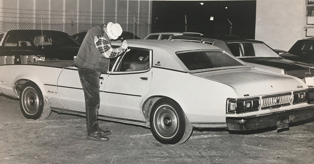 A policeman examines the yellow 1974 Mercury in which George Basmajian's bullet-riddled body was found. Basmajian was sitting in the backseat when he was shot nine times in the torso and face. One detective said the car was steaming up inside when it was discovered. Courtesy of the Providence Journal/William K. Daby.
