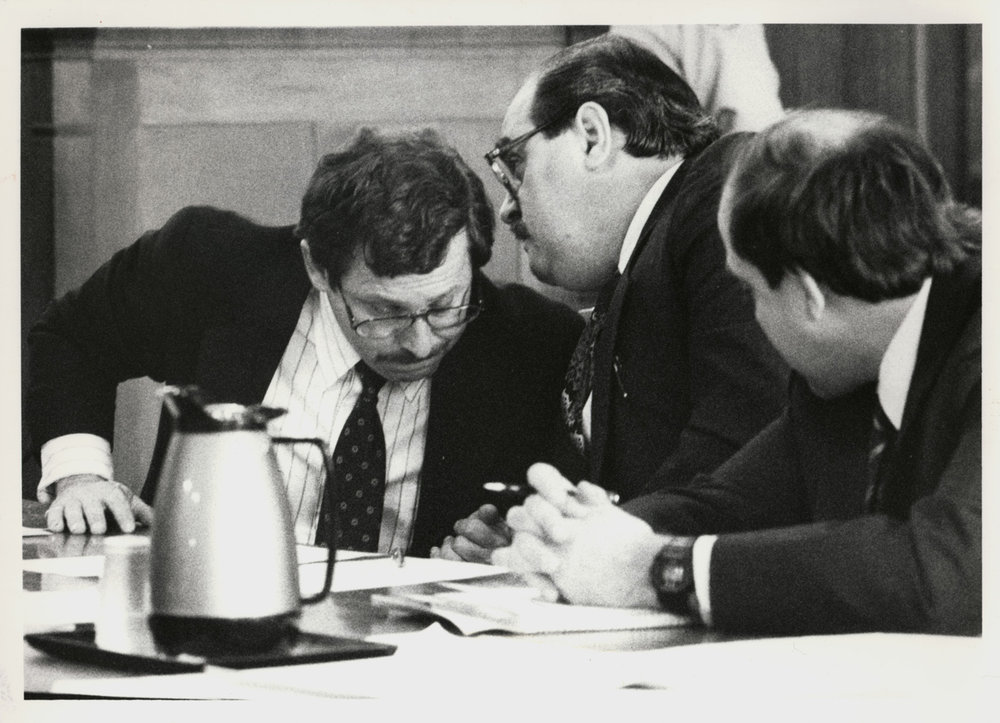 Bobo Marrapese, center, confers with lawyer Richard Egbert, left, while another of his lawyers listens in. Courtesy of the Providence Journal/Lawrence S. Millard.