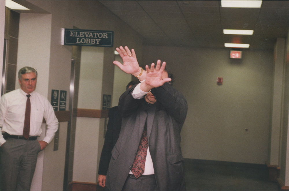 Robert Barbato hides his face in November 1991. Barbato's decades-long friendship with Bevilacqua drew media scrutiny when Bevilacqua became Chief Justice of the Rhode Island Supreme Court. Courtesy of The Providence Journal/Mary Murphy.