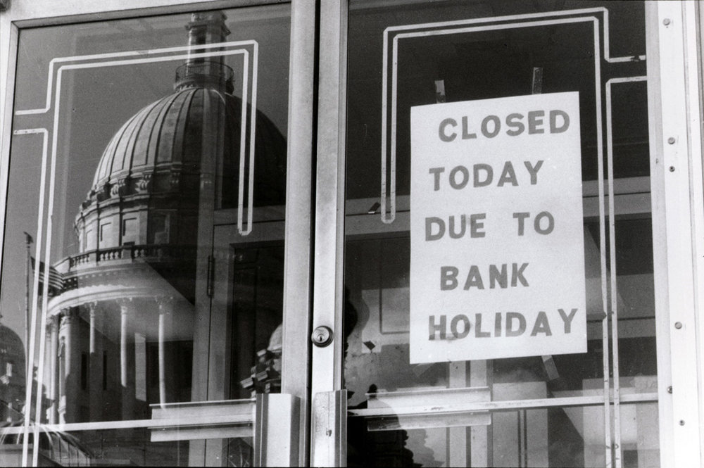 The State House is mirrored in the doorway of the State Employees Credit Union across the street. The credit union was among those that were closed as part of Governor Bruce Sundlun's banking freeze in 1991. Courtesy of The Providence Journal.
