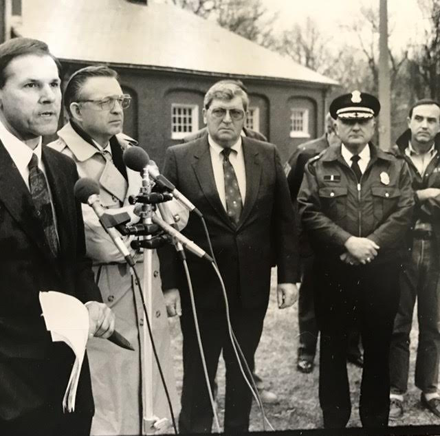 Tom Hughes of the FBI, far left, announces the Emerald Square Mall arrests at the Lincoln Woods state police barracks in 1991. Andrews is on the far right.  Courtesy of Brian Andrews.