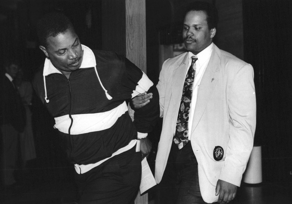 In 1991, surrounded by a phalanx of media, Sergeant Harris tries to pull away from a court officer just before being released on bond.  Courtesy of the Detroit Free Press.