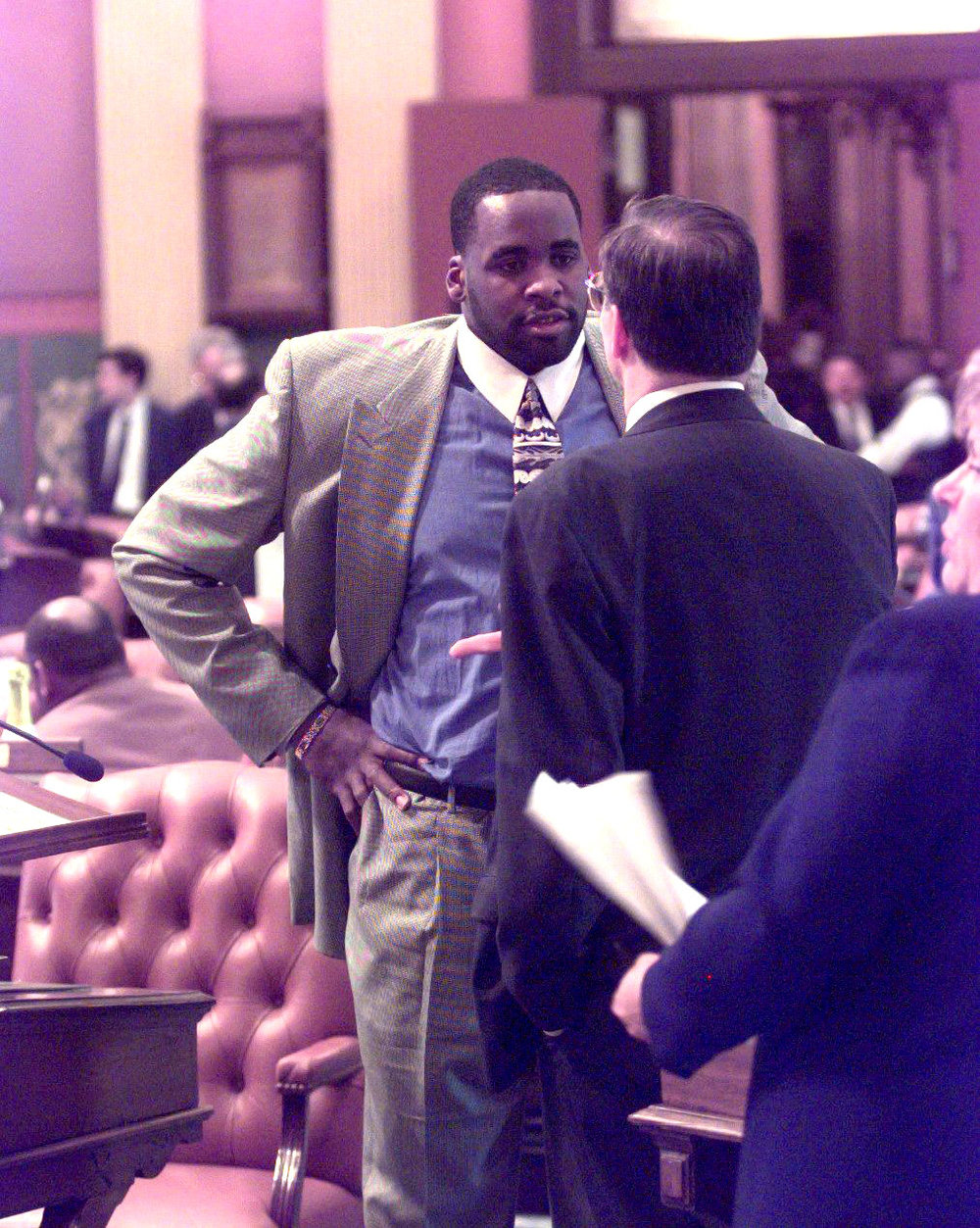 Kwame talks with a colleague on the floor of the House in March 1999.   He developed a reputation for working across racial and party lines.  Courtesy of the Detroit Free Press.